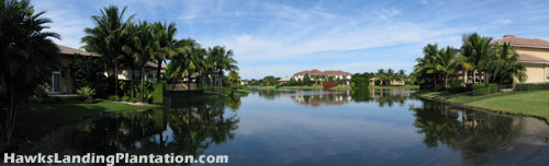 Lush tropical landscaping is visible across the lake vistas of Hawks Landing in Plantation, FL.